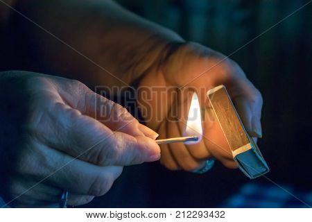 To light a match. The woman lights a match fire from a match.