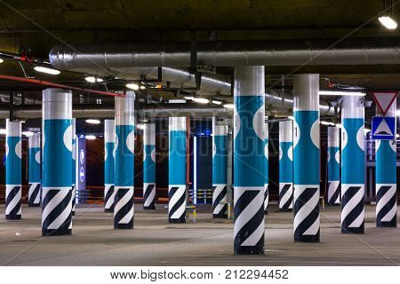 Underground asphalt parking garage interior with round blue columns neon lights in dark industrial building. Empty shopping center parking at night.
