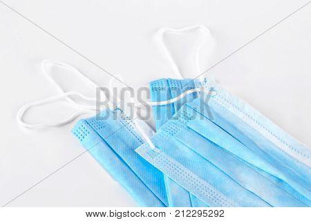Set of face protective masks. Blue medical surgical mask over grey background. Medicine and healthcare concept.