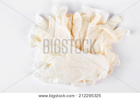 Pile of white medical gloves. Heap of thin latex medical gloves isolated on white background. Medicine and health care concept.