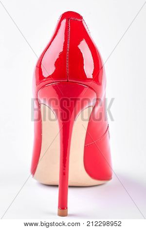 Female new lacquered high heel. Lady elegant red shoe on white background, back view.