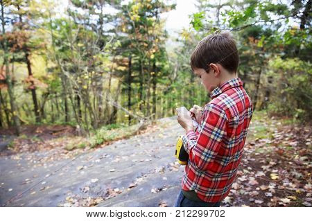 boy writes notes on the results of observations of nature. young boy scout scribbles notes outdoors. Discovery concept. copy space for your text