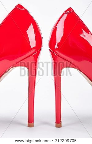 Pair of red lacquered female heels. Woman elegant red shoes o high heels isolated on white background. Classic heels on sale.