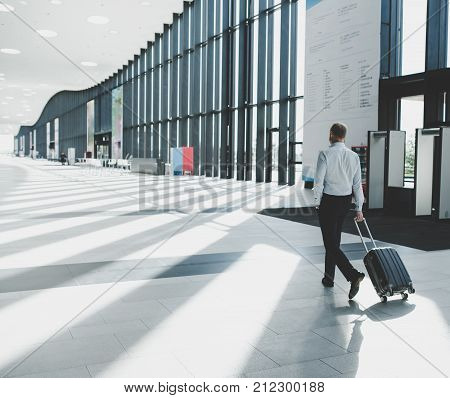 Business man in formal clothing walking with wheeled bag at airport terminal