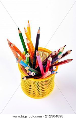 Multicolored pencils in metal pot. Yellow pen holder with colored pencils on white background, top view.