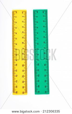 Yellow and green plastic rulers. Two fifteen centimeters rulers for measuring in school, isolated on white background. Vertical image of plastic rulers.