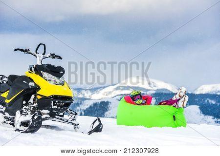 Rider on the snowmobile in the mountains ski resort in Amut Russia. The rider on the snowmobile in the mountains. the active drive. vacation in the mountains