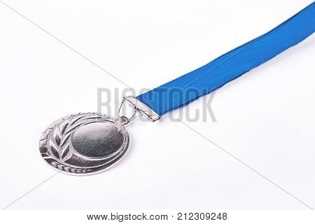 Champion silver medal, white background. Oympic silver medal on blue ribbon, isolated on white background. Symbol of championship and victory.
