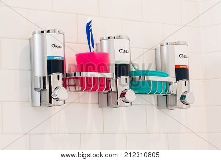 horizontal image of a stainless steel rack on white bathroom wall for shampoo and conditioner and shower gel  holder with tooth brush in a pink cup