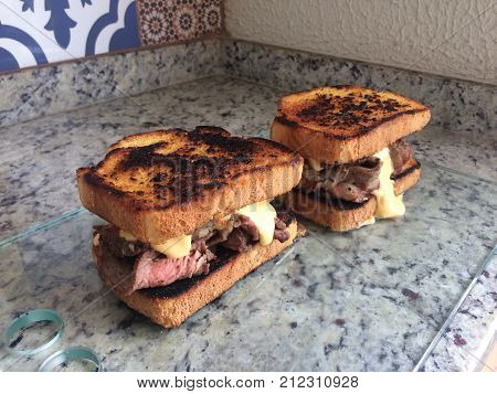 Sliced beef sandwiches with a lot of melted cheese