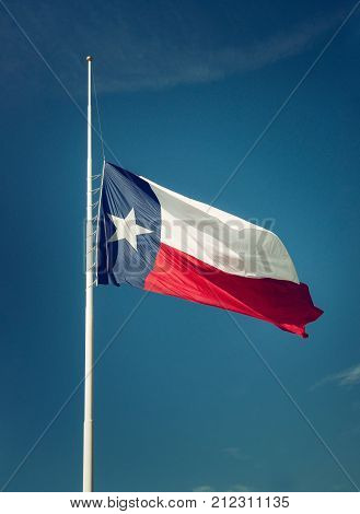 State flag of Texas flying at half-mast or half-staff on a flagpole. Blue sky background with copy space. Vintage filter effects.