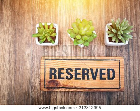 Wooden reserved sign on top of a wooden table in a restaurant Reservation seat at restaurant for dating on celebrate day concept. Reserved sign from top view decorate with little cactus and light