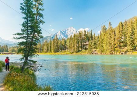 Banff August 2015 In this period of no rain a woman is taking a picture from this view point to Bow river near Banff to take with her a little peace of this paradise.