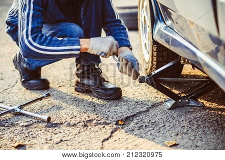 Jacking up a car to change a tyre after a roadside puncture with the hydraulic jack inserted under the bodywork raising the vehicle and the spare wheel balanced on the side. poster
