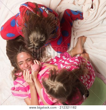 Nightwear fashion for girls. Children in pajamas have fun in bed top view. Happy childhood family love friendship. Bedtime slumber dream sleepover. Comfort home concept.