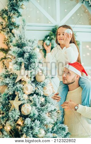 Girl Helping Father Decorating Christmas Tree, Holding Some Christmas Baubles
