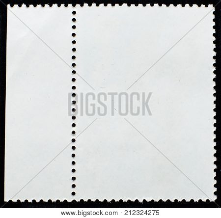 Old grunge posted stamp reverse side with the edge of the sheet isolated on black background