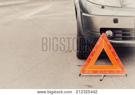 Auto assistance and insurance troubles while traveling concept. Broken car and auto triangle on road