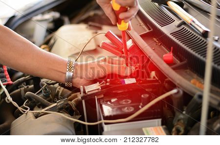 The Repairman Using The Screw Driver Fixing The Car Battery In Shop