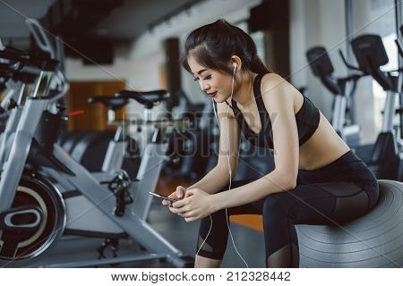Young asian woman athlete listening music with smartphone relax after break workout and cardio sport exercise at fitness gym on yoga ball for healthy lifestyle