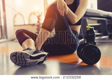 Woman excercise workout in gym fitness breaking relax holding protein shake bottle after training sport with dumbbell and healthy lifestyle bodybuilding.