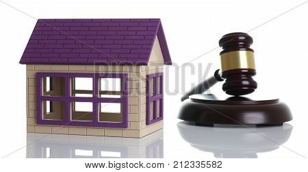 A judge hammer with miniature house isolated on a white background, the subject decision making in the real estate sphere of the hereditary inheritance strong will or property