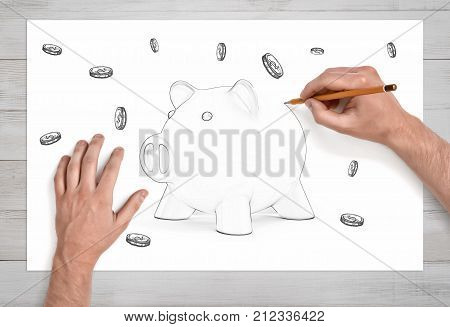 A pair of male hands in close view draws the last line on a pencil sketch of a piggy bank surrounded by many coins. Personal finances. Trust fund. Budget and money.