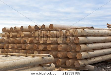 Cylindrical logs for log home, stacked in stack