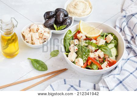 Vegan healthy salad with paprika tofu hummus and olives. Healthy vegan food concept.