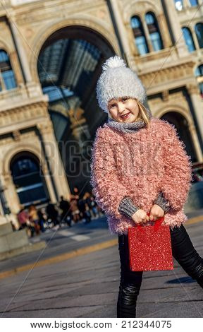 Rediscovering things everybody love in Milan. elegant girl with red shopping bag at Piazza del Duomo in Milan Italy standing
