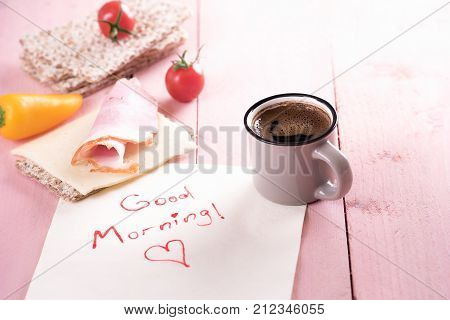 Healthy sandwich and good morning note - Simple healthy meal with whole-wheat crispbread tomatoes cheese meat and a cup of coffee on a napkin with a good morning message in the morning light.