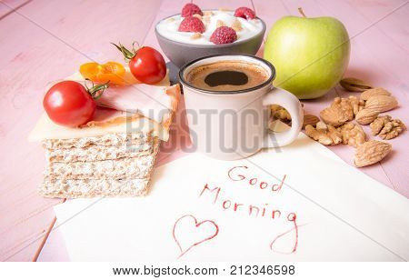 Healthy food and good morning message - First meal of the day with fruits nuts vegetables whole-wheat crispbread served with a cup of hot coffee near a napkin with the good morning text on it.