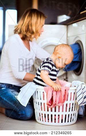 Young mother with a baby son doing housework. Beautiful woman and baby boy doing laundry. Baby boy in the laundry basket.