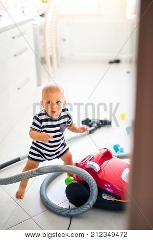 Cute baby boy with the hoover in the kitchen. Little boy playing with vacuum cleaner.