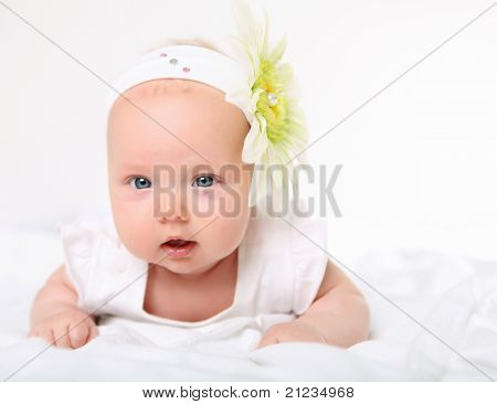Portrait of a baby girl with a flower on her head