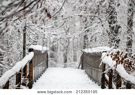 Old antique wooden foot bridge in a winter forest covered in snow as season concept background
