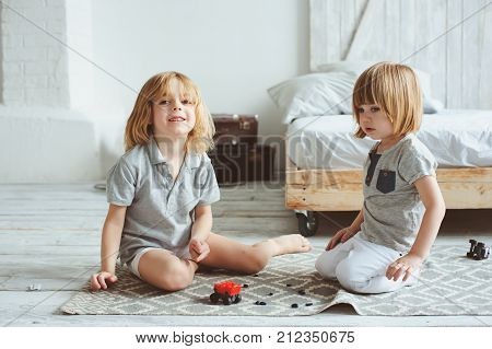 two happy siblings playing with toy cars at home in the morning. Casual lifestyle in bedroom