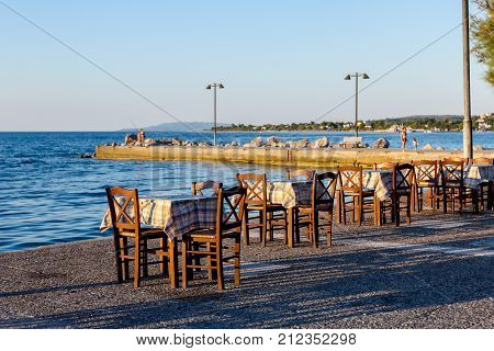 Chairs and tables in typical outdoor Greek tavern in sunset light with shadows near wharf.