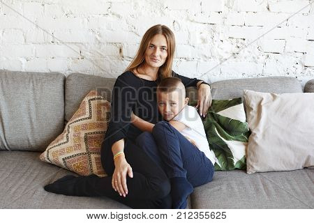 Mother with son resting at home. Coward schoolboy sheltering himself behind his mom's back sitting on couch and embracing her tight complaining of bullies at school can't stand up for himself