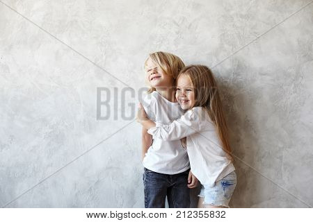 Joyful beautiful 5 year old female child with long straight hair hugging tight her elder brother both standing at blank wall and laughing. Puppy love between blonde boy and girl of preschool age