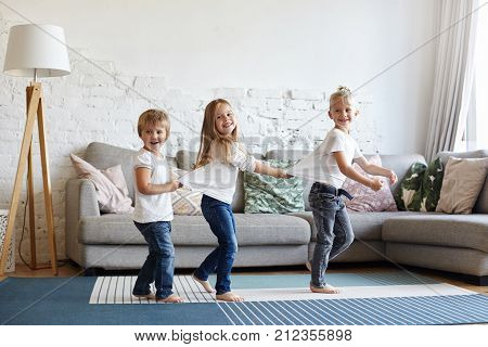 Picture of three excited children siblings in white t-shirts and jeansdancing barefooted on wooden floor at home. Two little girls standing in sequence with their blonde elder brother in the lead