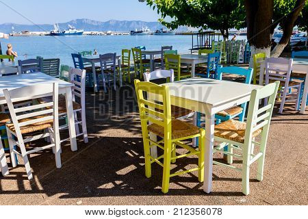 Chairs and tables in typical outdoor Greek tavern in morning sunlight with shadows near wharf.