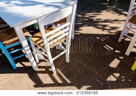 Chairs and tables are colored in typical outdoor Greek tavern in morning sunlight with shadows.