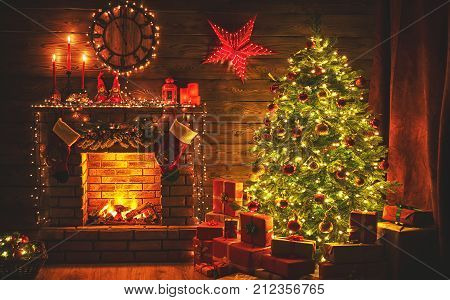 interior christmas. magic glowing tree fireplace gifts in dark at night
