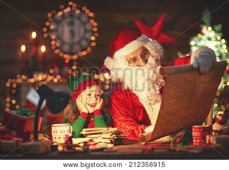 santa claus reads list of good children to little elf by fireplace and Christmas tree