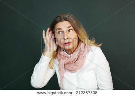 Frustrated elderly woman suffering from deafness trying hard to hear something. Curious senior female eavesdropping holding hand at her ear and listening attentivel. Difficulty in hearing