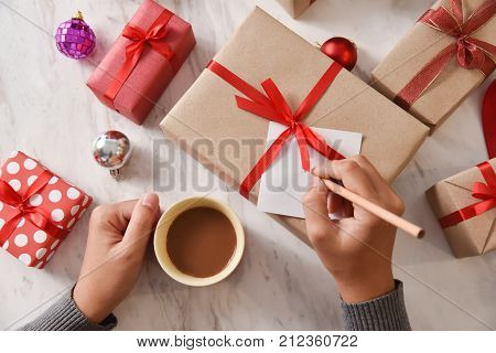 Female Hand writing greeting card on white marble table with red and brown gift boxes for Christmas and New year. Holding cup of coffee. Copy space. top view.