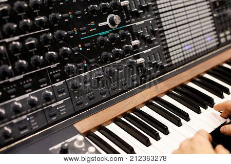 A musician at the keyboard of modern analog synthesizer. Selective focus.
