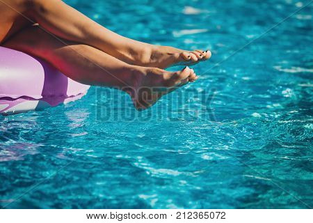 Woman's legs on the inflatable ring in the swimming pool. Summer Vacation. Enjoying suntan. Weekend on resort