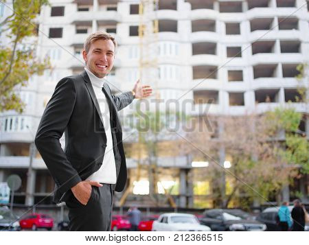 A young attractive guy in a black suit is standing on the street, smiling and showing his hand to an unfinished building. Outside.